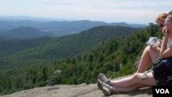 Dua orang pendaki beristirahat sembari menikmati pemandangan pegunungan Blue Ridge yang cantik.