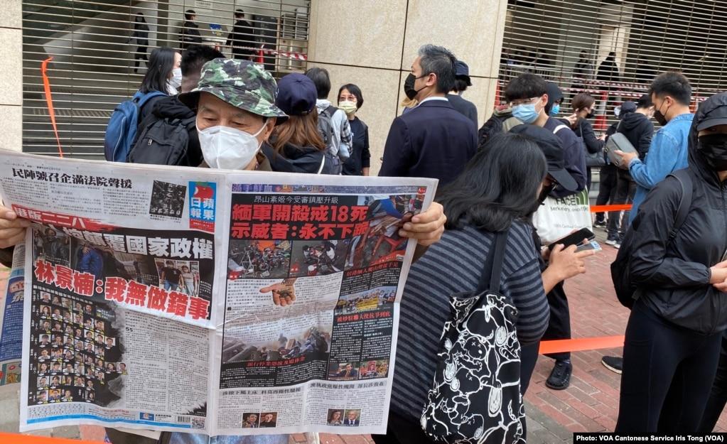 """手持香港《苹果日报》的香港市民梁先生在西九法院大楼外排队,他形容防疫限聚令使香港成为一个大监狱,3月1日逾千人排队声援47名被控国安法的民主派人士有如""""放监"""" (美国之音/汤惠芸)(photo:VOA)"""