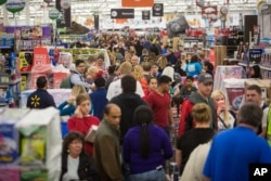 FILE - Customers save big at Wal-Mart's Black Friday shopping event in Rogers, Ark, Nov. 26, 2015.