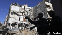 Các chiến binh phe nổi dậy đứng trước một ngôi nhà bị tàn phá trong vụ oanh kích