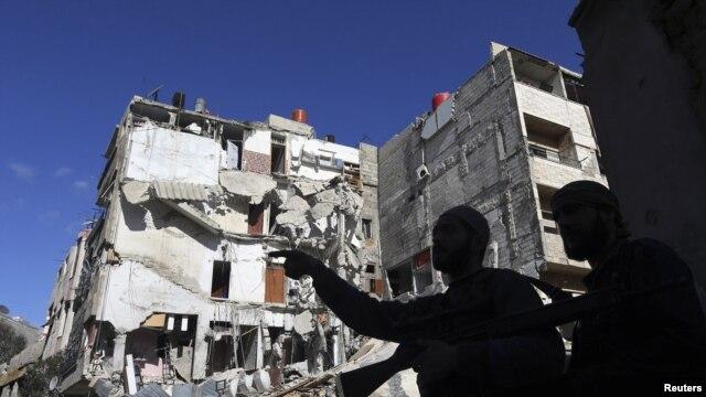20일, 수도 다마스쿠스 인근에서 시리아군의 공습으로 파괴된 건물 앞에 서 있는 시리아 반군 병사들.