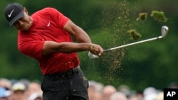 Tiger Woods hits on the 12th hole during the final round for the Masters golf tournament, April 14, 2019, in Augusta, Georgia.