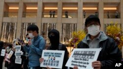"Protesters wearing masks hold placards reads"" Close the border, say no to China"" during a protest at a mall in Hong Kong, Tuesday, Feb. 4, 2020. Hong Kong on Tuesday reported its first death from a new virus, a man who had traveled from the mainland city…"