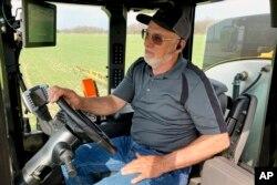 Petani Rick Clifton mengendarai traktor untuk menyemprotkan herbisida di salah satu ladangnya di Orient, Ohio, 5 April 2021. (AP)
