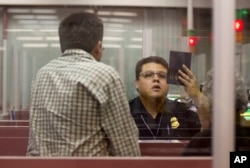 FILE - A Customs and Border Protection officer checks the passport of a nonresident visitor to the United States inside immigration control at McCarran International Airport, in Las Vegas, Dec. 13, 2011.