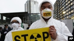 A Greenpeace activist holds a placard during a demonstration outside Japan's Prime Minister Yoshihiko Noda's official residence in Tokyo, criticizing the government's declaration of cold shutdown at the Fukushima nuclear power plant, December 16, 2011.