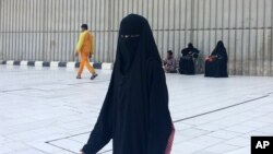 FILE - A veiled woman walks in Mecca, Saudi Arabia, where society is governed by a mix of ancient customs and conservative interpretations of Islam. Most women cover their faces and by law must wear long, flowing black abayas in public.