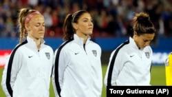 Atlet sepakbola putri AS, dari kiri ke kanan, Becky Sauerbrunn, Hope Solo dan Carli Lloyd, dalam perkenalan tim sebelum pertandingan melawan Kosta Rika (10/2) di Frisco, Texas.