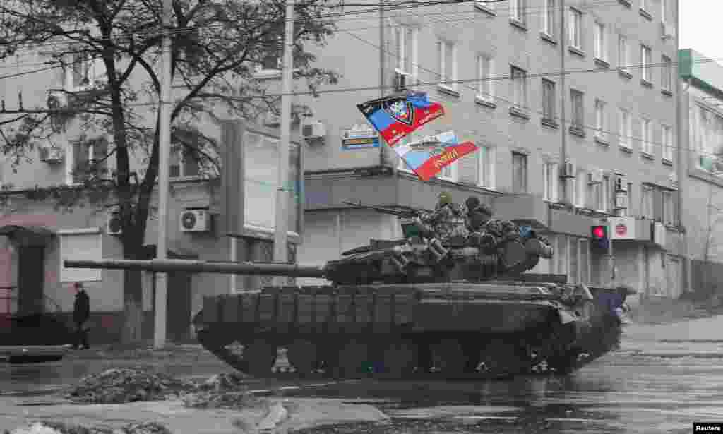 Pro-Russian separatists ride on a tank in Donetsk, eastern Ukraine, Feb. 1, 2015.