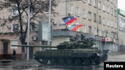 FILE - Pro-Russian separatists ride on a tank in Donetsk, eastern Ukraine, Feb. 1, 2015.