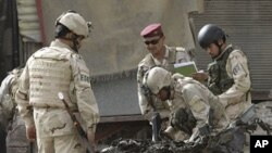 Security force personnel inspect a destroyed car at the scene of a car bomb attack in Baghdad, Iraq, Sunday, May 22, 2011