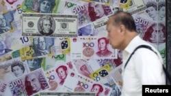 Ảnh tư liệu - Một người đàn ông đi ngang qua cửa hàng thu đổi ngoại tệ ở Hong Kong, ngày 13 tháng 8 năm 2015.