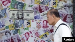 FILE - A man walks past an advertisement promoting China's renminbi (RMB) or yuan, U.S. dollar and Euro exchange services at foreign exchange store in Hong Kong, China, Aug. 13, 2015.