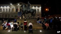 Residents sent running into the street after a magnitude-8.3 earthquake sit next to an equestrian statue in the main square of Santiago, Chile, Sept. 16, 2015.