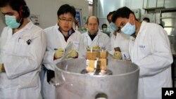 지난해 1월 이란 테흐란 인근 우라늄 농축 시설에서 국제원자력기구 IAEA 검사관들과 이란 기술자들이 농도 20%의 농축 우라늄 생산을 중단시키는 작업을 하고 있다. (자료사진)