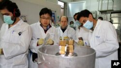 FILE – Iran, saying it has halted its most sensitive uranium enrichment work, objects to the U.S. adding new targets for sanctions. Here, Iranian technicians prepare to cut connections between twin cascades at Iran's Natanz nuclear facility, Jan. 20, 2014.
