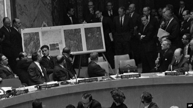 In this October 25, 1962 file photo, U.S. Ambassador Adlai Stevenson, far right, describes aerial photographs of launching sites for intermediate range missiles in Cuba during an emergency session of the United Nations Security Council at U.N. Headquarter