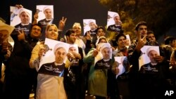 FILE - Iranians hold posters of President Hassan Rouhani, while welcoming Iranian nuclear negotiators upon their arrival from Geneva at Mehrabad Airport in Tehran Nov. 24, 2013.