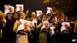 Eronliklar Jenevadagi muzokaralardan qaytgan delegatsiyani prezident suratlari bilan kutib oldi. 24-noyabr 2013-yil.