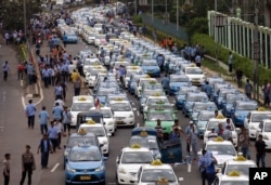 Taxis are lined up during a protest against competition from ride-hailing apps such as Uber and Grab at the main business district in Jakarta, Indonesia, March 22, 2016.