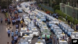 FILE - Taxis are lined up during a protest against competition from ride-hailing apps such as Uber and Grab at the main business district in Jakarta, Indonesia, March 22, 2016.