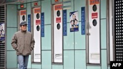 FILE - A man walks past public toilets in Shanghai during the World Toilet Day, Nov. 19, 2009.