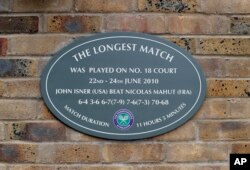 FILE - This Tuesday, July 4, 2017 file photo shows a plaque at the Wimbledon Tennis Championships in London, noting the site of John Isner's record-breaking 70-68 fifth-set victory over Nicolas Mahut in 2010. The All England Club said Friday Oct. 19, 2018
