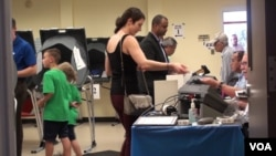 Voters checking in to vote in Houston. (G. Flakus/VOA)