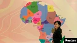 Une Chinoise passe devant une carte de l'Afrique, Shanghai, 14 mai 2007.