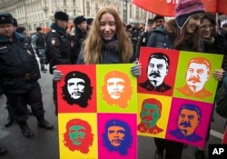 Communist party supporters carry Andy Warhol-style portraits of Cuban Revolution hero Ernesto 'Che' Guevara, center, and Soviet leader Josef Stalin, right, during a demonstration marking the 100th anniversary of the 1917 Bolshevik revolution in Moscow, Nov. 7, 2017.