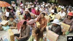 People sit as they receive flood donations at downtown Phnom Penh, Thursday, Oct. 13, 2011.