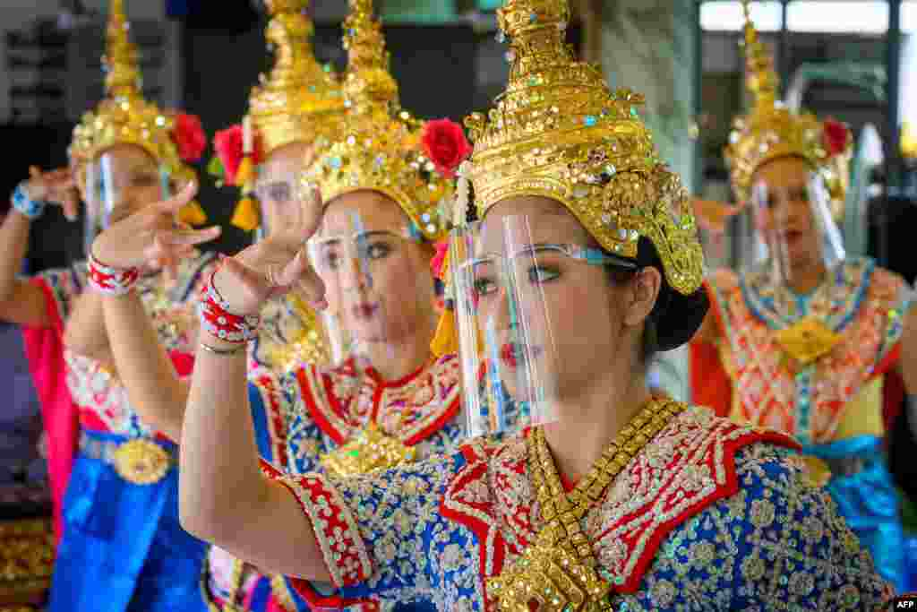 Traditional Thai dancers wearing protective face shields perform at the Erawan Shrine, which was reopened after the Thai government relaxed measures to combat the spread of the COVID-19 novel coronavirus, in Bangkok.