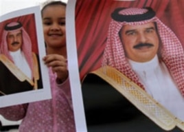 A girl holds up a picture of Bahrain's King Hamad bin Isa Al Khalifa in Muharraq, Bahrain, February 16, 2011, during a gathering to counter three days of anti-government demonstrations