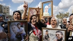 Palestinian women hold portraits of relatives held in Israeli jails during a protest calling for the release of Palestinian prisoners, Nablus, West Bank 6 Oct. 2009