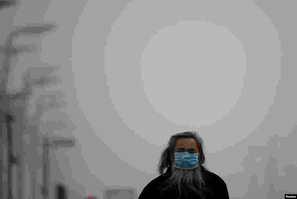 A man wearing a mask makes his way amid thick haze in Beijing, Feb. 25, 2014.