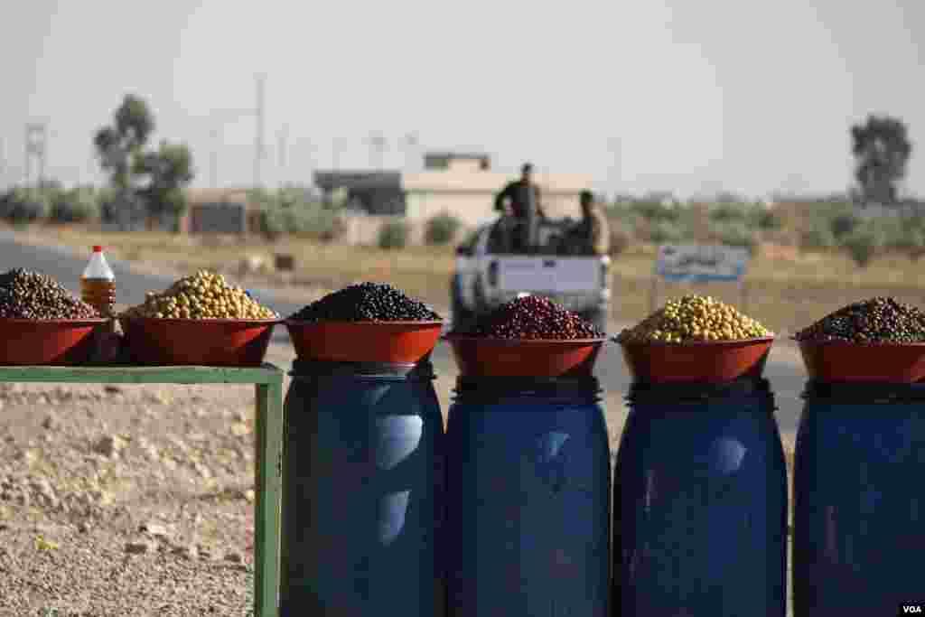 Tentara Peshmerga mundur setelah membeli zaitun yang tadinya hanya tersedia untuk para militan Negara Islam (ISIS), karena warga lokal tidak mampu membeli buah yang termasuk barang mewah itu di bawah kekuasaan mereka (23/11). (H.Murdock/VOA)