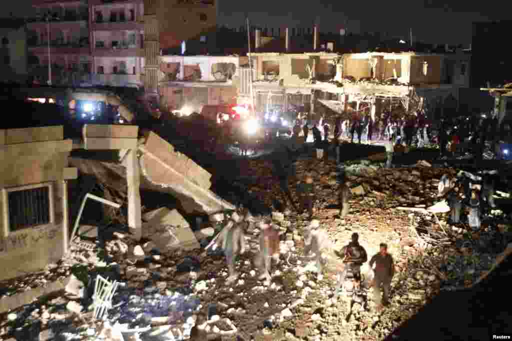 Residents gather at a site hit by what activists say was a Scud missile from forces loyal to Syria's President Bashar al-Assad in Raqqa, Nov. 28, 2013.
