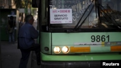 "A passenger boards an electric bus displaying a sign that reads ""MasXCoche. Free Service"" in Mexico City, Mexico, April 5, 2016."