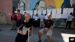 Dos electores aguardan antes de depositar su voto mientras otros examinan listas para ver dónde deben votar durante los comicios locales en Caracas, Venezuela, el domingo 9 de diciembre de 2018.