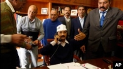 Aam Aadmi Party leader Arvind Kejriwal talks on phone as he assumes office of the Chief Minister of Delhi, New Delhi, Dec. 28, 2013.
