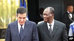 Ivory Coast's President Alassane Ouattara walks with French Prime Minister Francois Fillon at the presidential palace in Abidjan, July 15, 2011