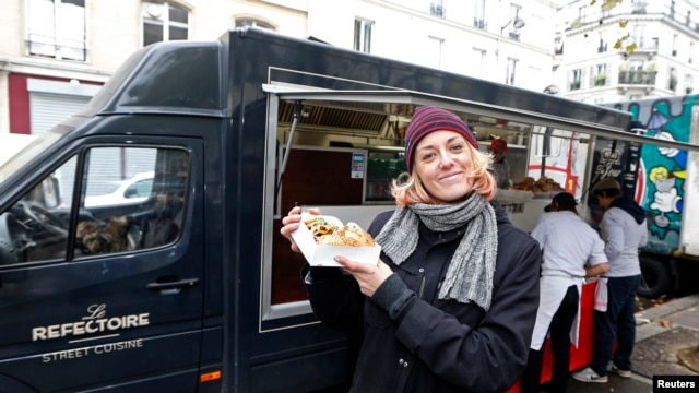 French Valentine Davase poses in front of her 'Le Refectoire' food truck in Paris November 16, 2012.