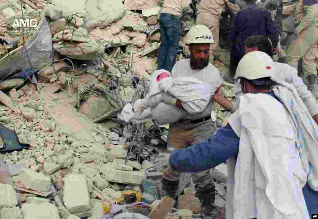 Civil defense rescue workers carrying the body of a victim of a Syrian government airstrike, Aleppo, April 6, 2014.