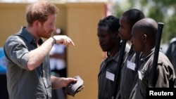 Britain's Prince Harry (L) chats to students at the Southern African Wildlife College, near the Orpen Gate of the Kruger National Park in the Limpopo province, South Africa, Dec. 2, 2015.