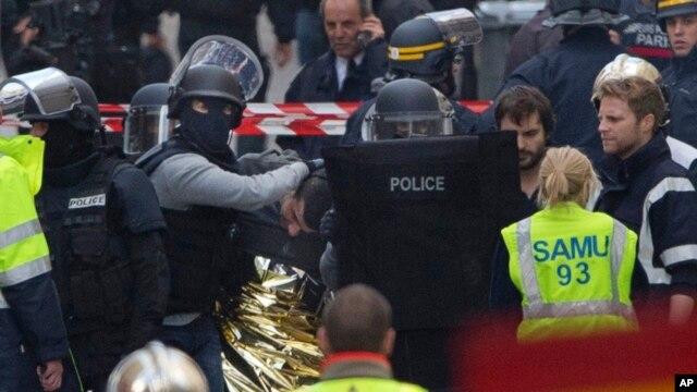 Cảnh sát bịt mặt bắt giữ một người đàn ông trong vụ đột kích vào một chung cư ở Saint-Denis, gần Paris, ngày 18/11/2015.
