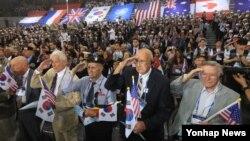 27일 서울 올림픽공원 핸드볼경기장에서 열린 '정전협정 64주년 및 유엔군 참전의 날' 기념식에서 6·25 참전용사들이 국기에 대한 경례를 하고 있다.