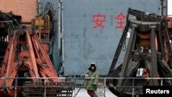 지난 2010년 북-중 접경 도시인 단둥 항구에서 중국인 노동자가 북한에서 들여온 석탄을 선적하기 위해 대기 중이다.