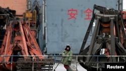 在辽宁省丹东港,一名装卸工等待把从朝鲜进口的煤装上卡车。(资料照)
