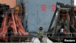 북-중 접경 도시인 단둥 항구에서 중국인 노동자가 북한에서 들여온 석탄을 선적하기 위해 대기 중이다. (자료사진)