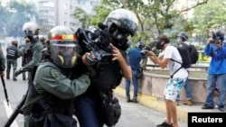 Members of the press, some pushed away with shields, are prevented by Venezuela's Bolivarian National Guard to get access to the Federal Legislative Palace.